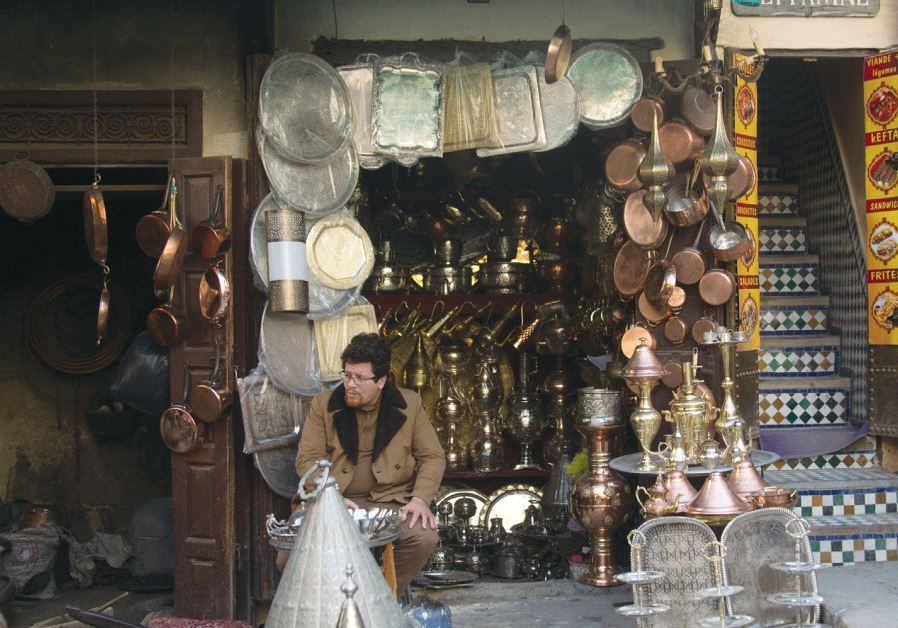 A merchant sits in front of a brassware shop in the Fez medina. Credit: Sarah Levi