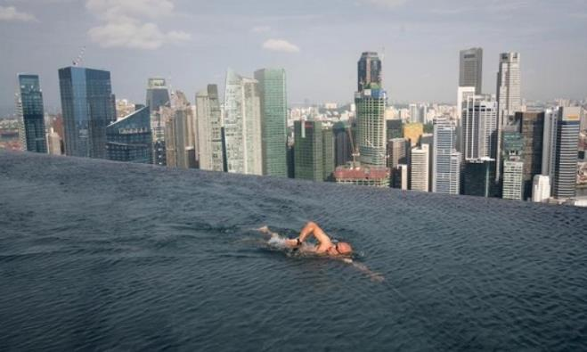 A guest swims in the infinity pool of the Skypark that tops the Marina Bay Sands hotel in Singapore
