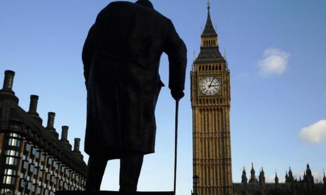 The statue of former Prime Minister Winston Churchill is silhouetted in front of parliament