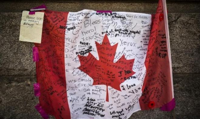 A Canadian flag is seen with messages of condolences at a makeshift memorial to honor Nathan Cirillo