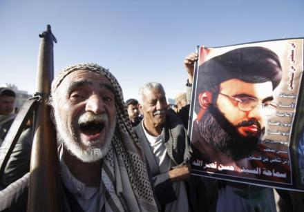 A Houthi militant shouts slogans as he stands next a poster of Hezbollah leader Hassan Nasrallah
