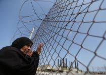 A Palestinian woman stands by a fence during a protest calling for an end to the power crisis, outsi