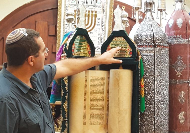 Dr. Yinon Elmakias lectures about the Torah scrolls in Hebron's Avraham Avinu synagogue, some of them dating back almost 500 years (Ben Bresky)