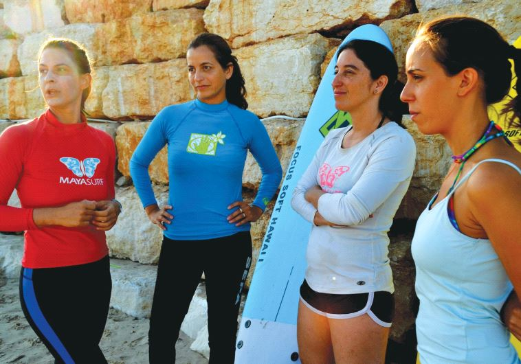 Instructor Sivan Amir (in red) briefs students on the day's waves before they enter the water (Inbal Aharoni)