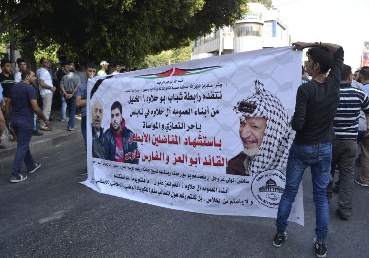 Young Palestinians raise poster, offering condolences to Halawa family. (Credit: Udi Shaham)